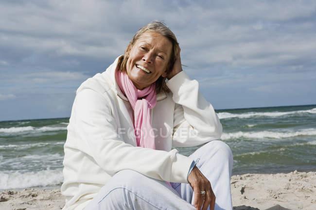 Retrato de mulher senior sorridente sentados na praia — Fotografia de Stock