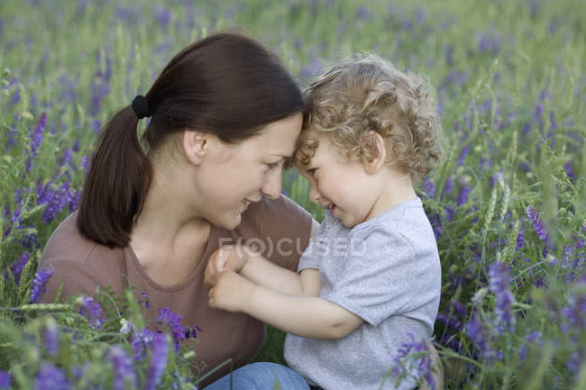 A woman and a young boy sitting face to face in a field — Stock Photo