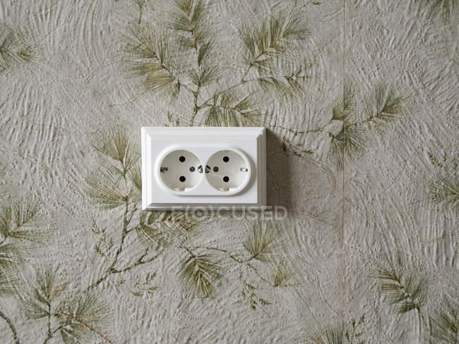 Электрической розетке на винтажные цветочные обои — стоковое фото