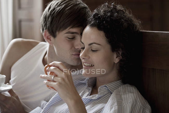 Couple sitting in bed with cups of tea in morning — Stock Photo