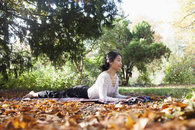 Вид сбоку улыбающейся женщины, лежащей на одеяле для пикника и занимающейся йогой в осеннем парке — стоковое фото