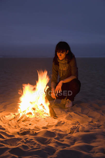 A woman staring into a fire burning on a beach — Stock Photo