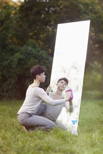 Side view of woman cleaning mirror while crouching on grassy field at park — Stock Photo