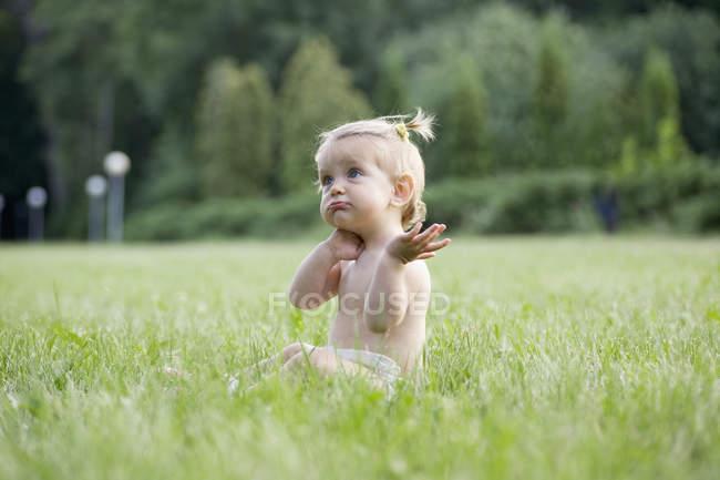 Девочка, сидящая на траве в подгузнике и смущенно выглядящая — стоковое фото