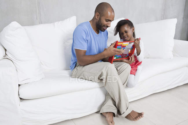 Father showing little daughter how to use abacus on sofa — Stock Photo