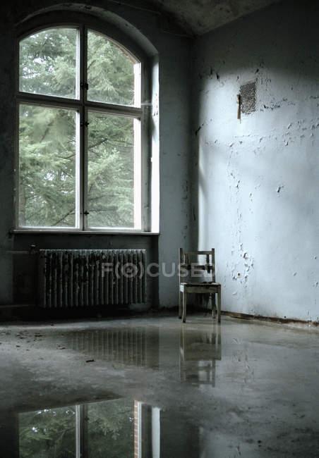 Внутрішній вигляд занедбаного номер з стілець bt вікно — стокове фото
