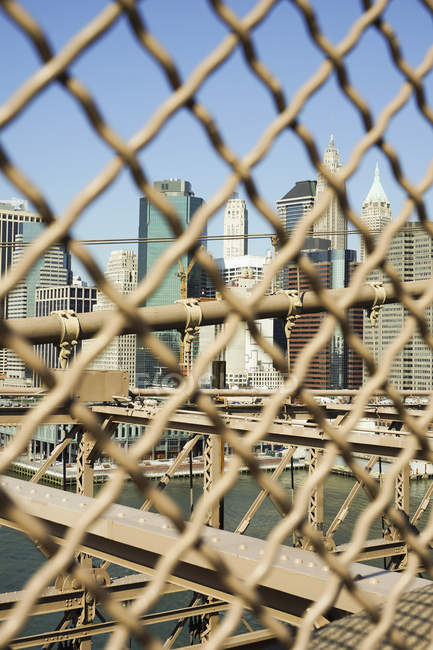 Rascacielos vistos a través de una cerca de eslabones de cadena en un día soleado - foto de stock
