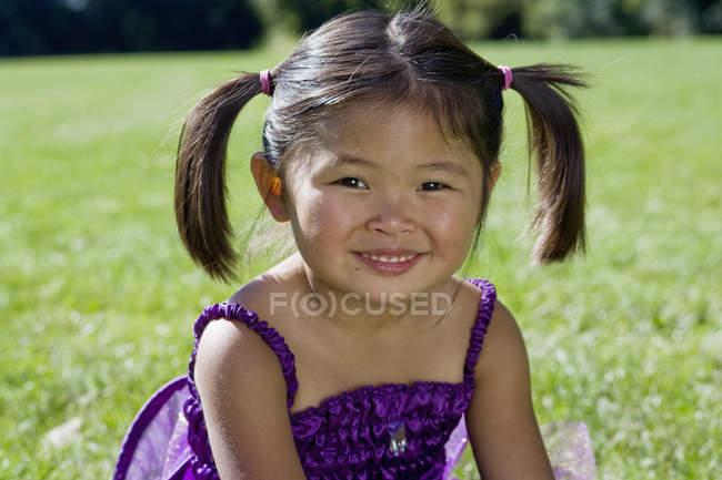Улыбающаяся маленькая девочка сидит на траве и смотрит в камеру — стоковое фото