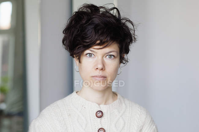 Portrait of frowning woman with short hair looking at camera — Stock Photo
