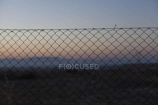 Цепной забор на фоне закатного неба — стоковое фото