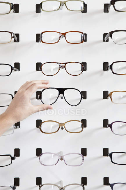 Crop hand choosing pair of glasses in eyewear store — Stock Photo