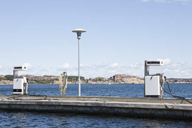 Petrol pumps on pier over water — Stock Photo