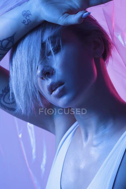 Чувственная молодая женщина позирует с рукой на голове на цветном фоне — стоковое фото