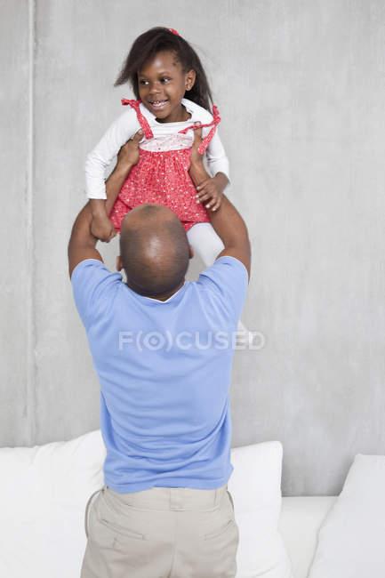 Hija sonriente del holding hombre alto - foto de stock