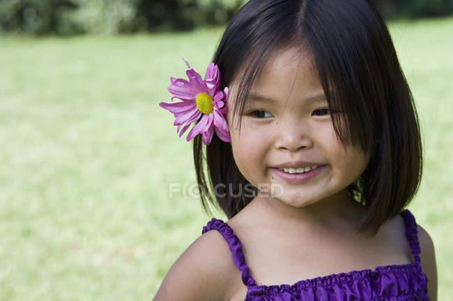 Портрет дівчинка з квіткою позаду вуха стоячи на Луці — стокове фото