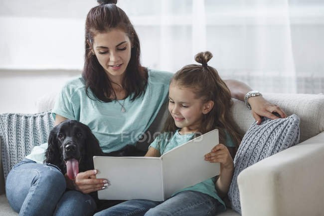 Smiling girl reading book by mother and dog on sofa at home — Stock Photo