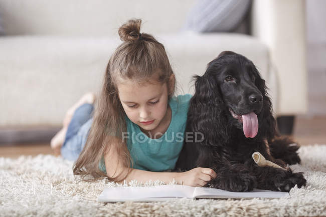 Cute girl reading book while lying with dog on rug at home — Stock Photo
