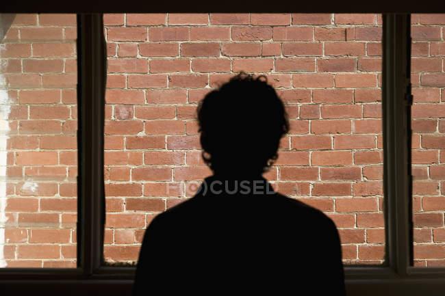 Silhouette eines Mannes, der durch Fenster auf Ziegelmauer blickt — Stockfoto