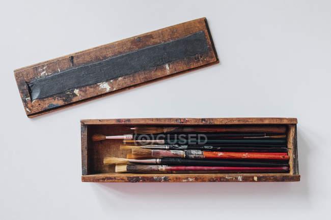 Direttamente sopra la vista di pennelli in caso di legno su sfondo bianco — Foto stock