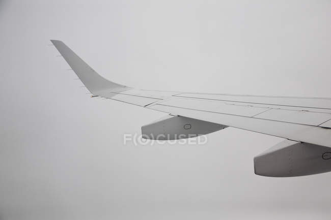 Crop wing of plane over cloudy sky — Stock Photo