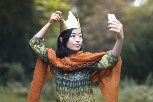Портрет жінки носять папір корони беручи selfie з смартфон в парку — стокове фото