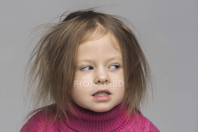 Porträt eines süßen Mädchens mit unordentlichem Haar, das vor grauem Hintergrund wegschaut — Stockfoto