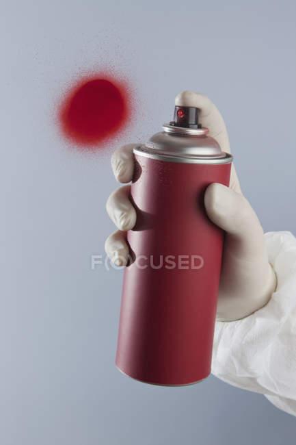Mano de cultivo con pintura aerosol rojo - foto de stock