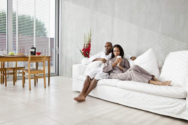 Pareja joven relajarse en un sofá por la mañana - foto de stock
