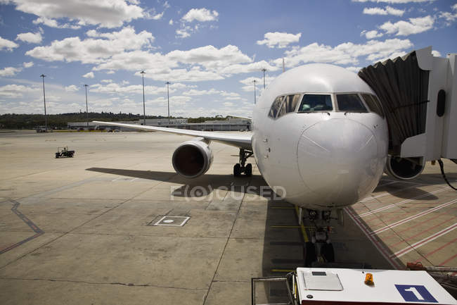 Airplane at airport tarmac connected to passenger boarding bridge — Stock Photo
