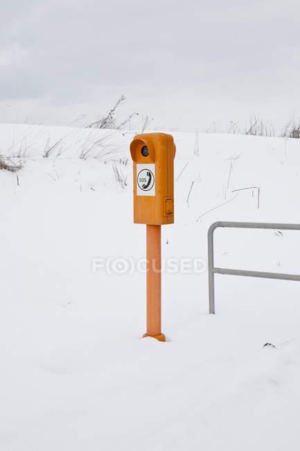 Poteau avec un téléphone d'urgence au milieu de la pente recouverte de neige — Photo de stock