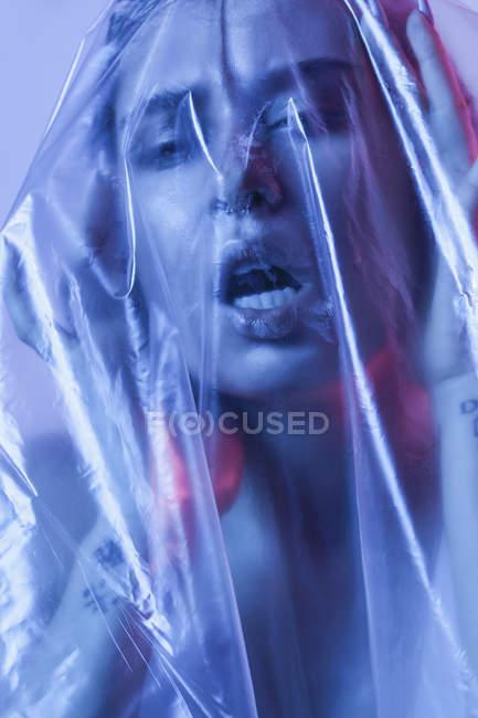 Retrato de cerca de una joven sensual envuelta en plástico - foto de stock