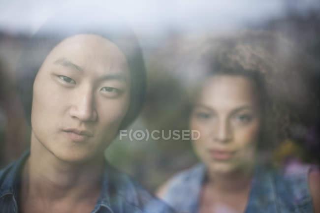 Retrato de casal olhando para a câmera vista através da janela de vidro — Fotografia de Stock