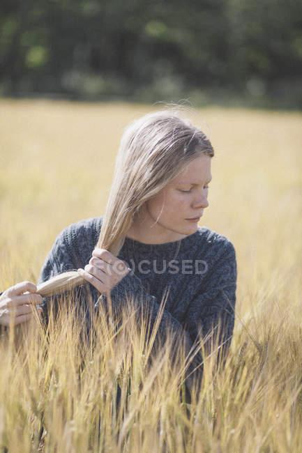 Donna premurosa che tiene i capelli lunghi in mezzo campo e guardando in basso — Foto stock