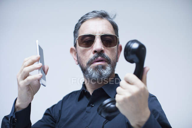 Portrait of businessman in sunglasses looking at telephone receiver and holding smartphone against white background — Stock Photo
