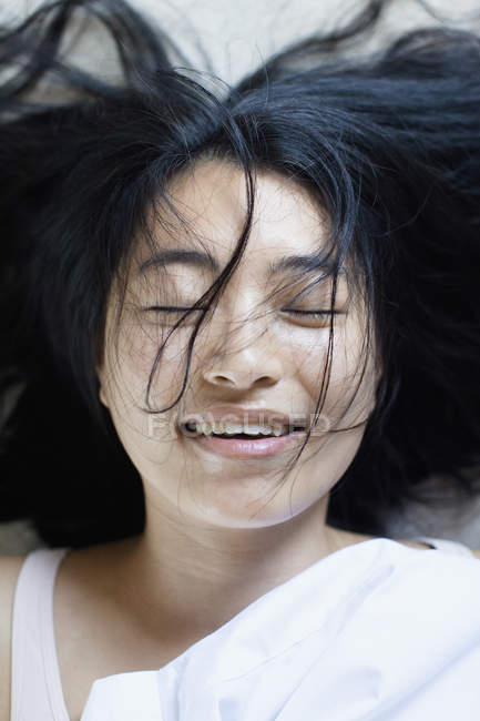 Portrait of smiling young woman with closed eyes and messy hair lying on bed — Stock Photo