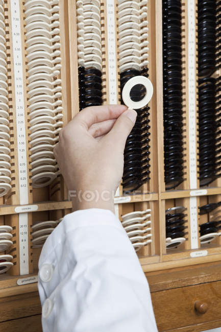 Crop optometrist's hand selecting test lens from rack — Stock Photo