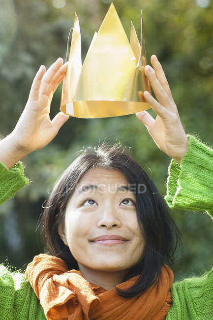 Retrato de mulher sorridente olhando para a coroa de papel nas mãos — Fotografia de Stock