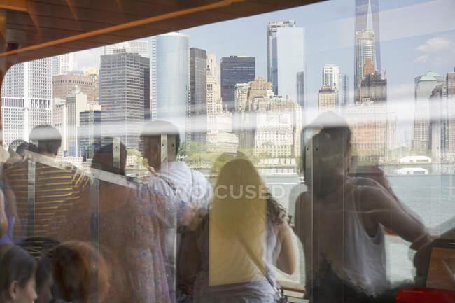 Reflexion von Menschen auf der Fähre, die Wolkenkratzer betrachten — Stockfoto