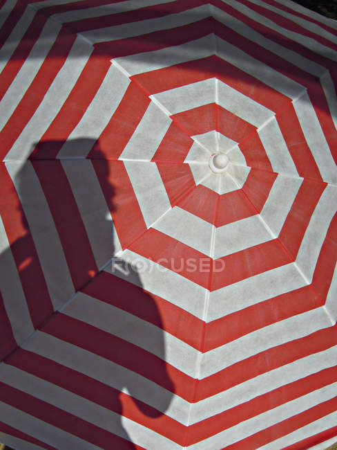 Shadow of person on red striped umbrella — Stock Photo