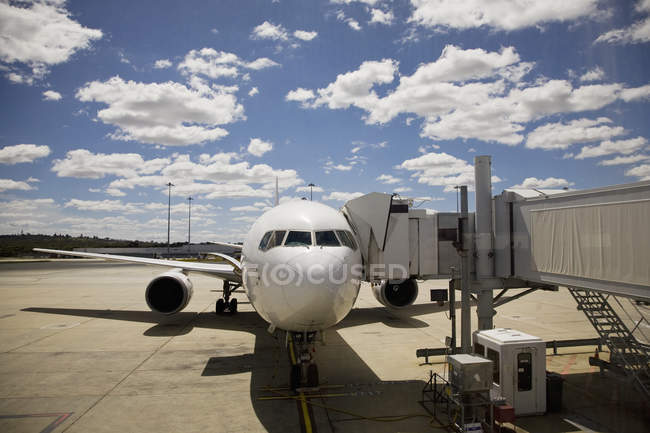 Airplane connected to passenger boarding bridge over scenic cloudscape — Stock Photo