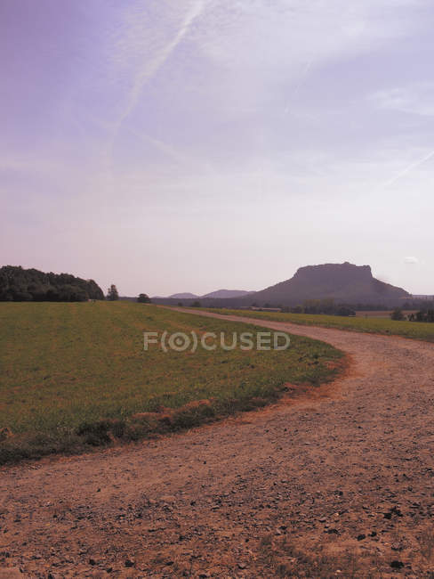 Vista panorâmica para a estrada em meio ao campo gramado contra o céu — Fotografia de Stock