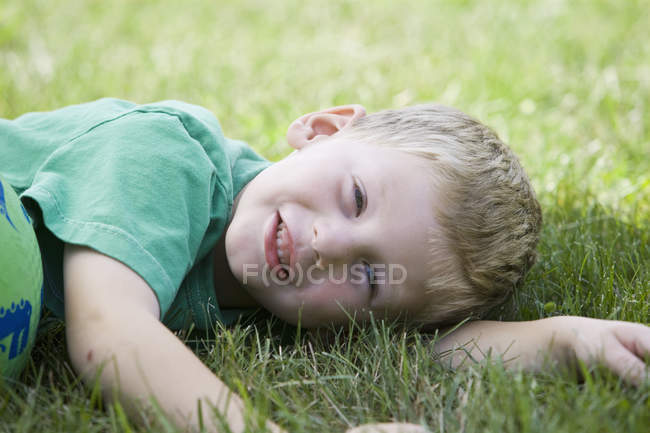 Smiling little boy lying on side in grass — Stock Photo