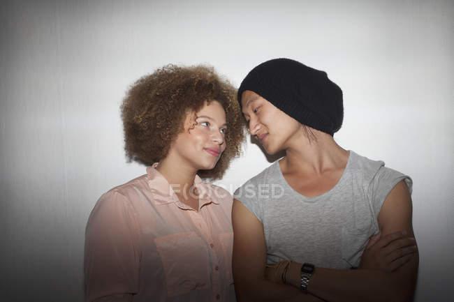 Lächelndes junges Paar steht gegen Wand — Stockfoto