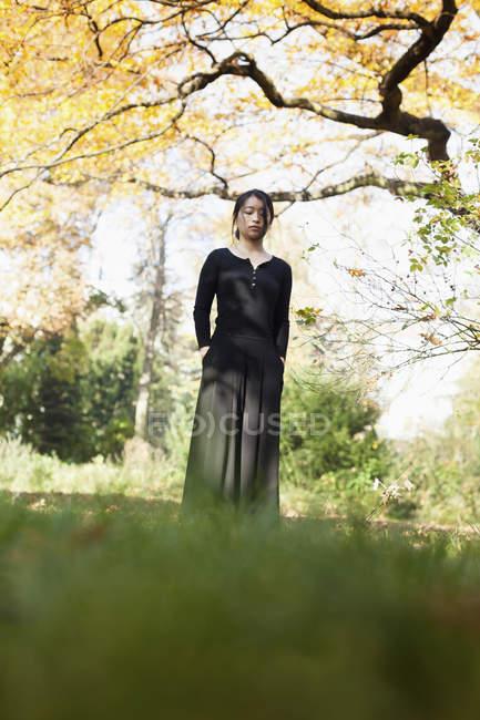 Surface niveau vue de femme avec des yeux fermés, debout sur la pelouse au parc — Photo de stock