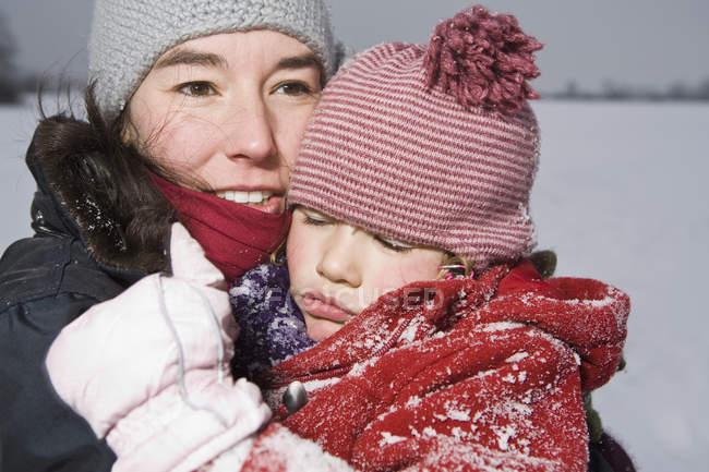 Uma mulher que carrega a filha dormir, ao ar livre, retrato — Fotografia de Stock