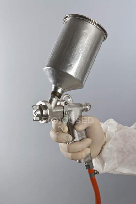 Cultivo de mano en guante con Pistola aerográfica - foto de stock