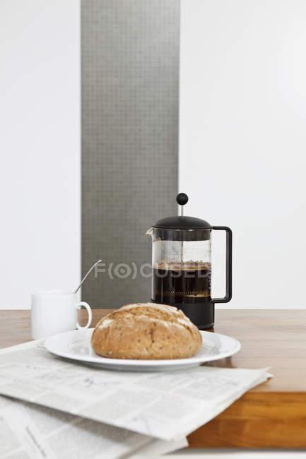 Натюрморт французской прессы с хлебом и чашкой кофе на газете — стоковое фото