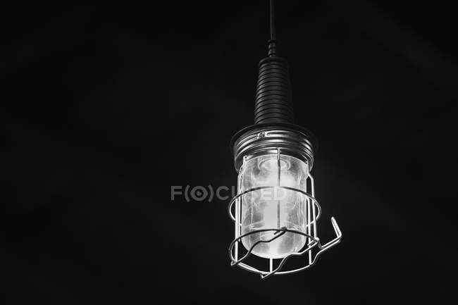 Illuminated light bulb hanging in dark room — Stock Photo