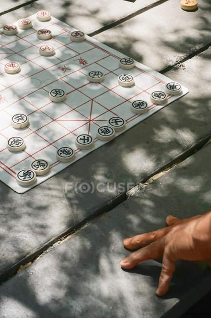 Recortar imagen de persona jugando al ajedrez chino en mesa - foto de stock
