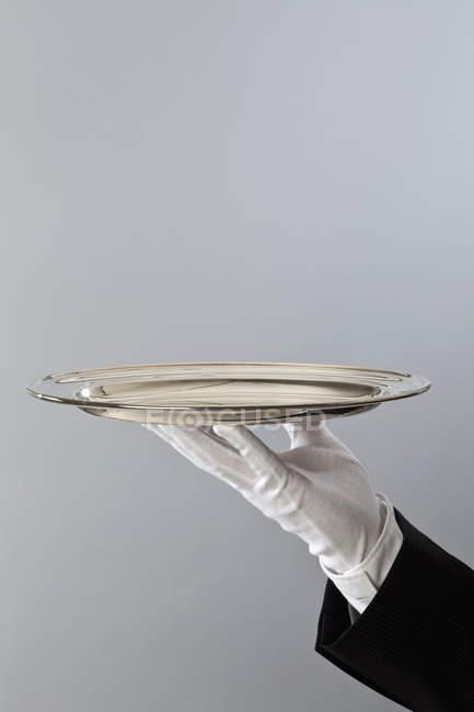 Crop butler's hand holding sliver platter — Stock Photo